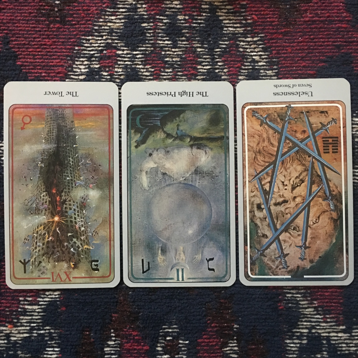 The Tower (reversed), The High Priestess (reversed), and Seven of Swords (reversed)